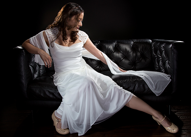 Bridal modeling modern fashion trend of simple but elegant thin wedding dress in retro or art deco style.  Bride on couch with shoulder scarf and bridal gown.