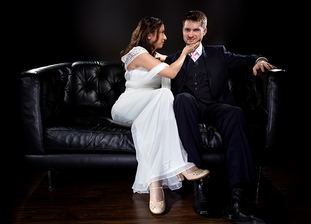 Engaged couple wearing modern wedding suit and bridal dress in a classical retro fashion style.  The stylish groom and bride are sitting on a leather couch in a studio.